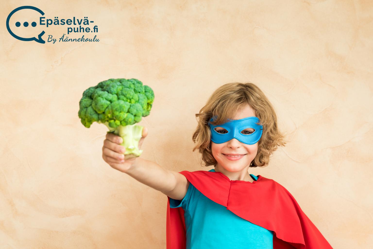 Lapsi pukeutunut supersankariksi ja pitelee parsakaalia kädessään